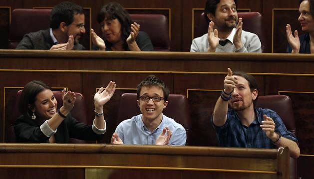 Los diputados de Podemos Irene Montero, Iñigo Errejón, y Pablo Iglesias aplauden desde su escaño tras aprobarse la paralización del calendario de implantación de la LOMCE.