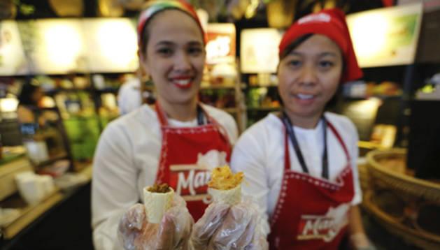Dos cocineras filipinas muestran una de sus creaciones en Madrid Fusión Manila 2016.
