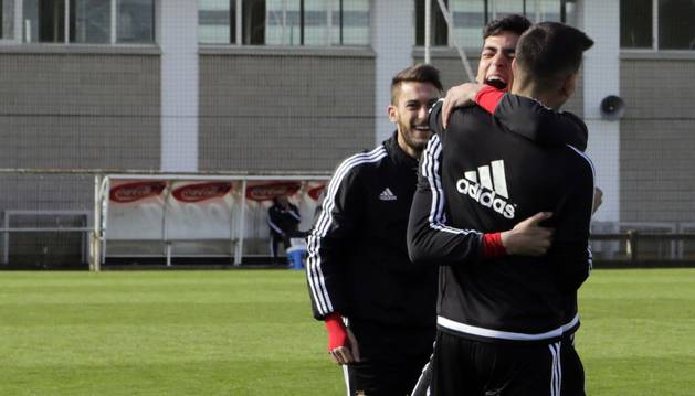 Merino abraza a un compañero en un momento del entrenamiento de ayer ante la mirada sonriente de Roberto Torres.
