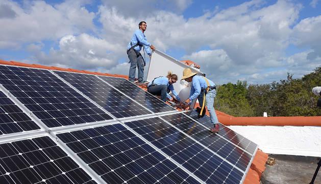 Varios trabajadores instalan unas placas solares.