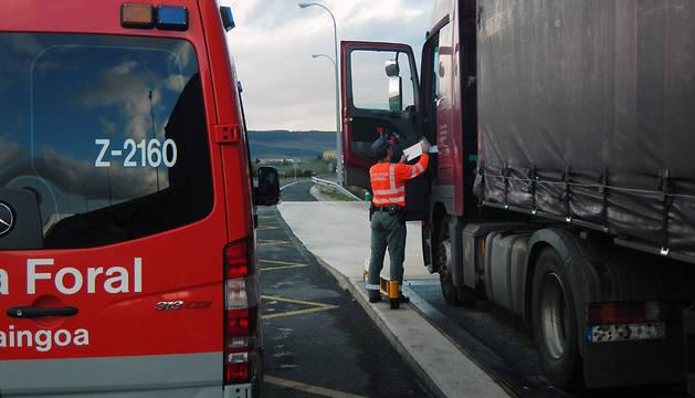 Un agente de la Policía Foral realiza un control a un camión.