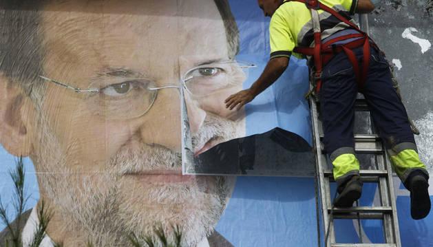 Un trabajador pega un cartel, en una campaña electoral anterior.