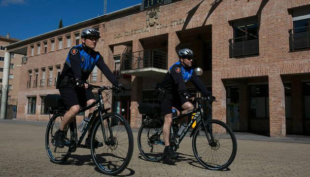 Los dos agentes que ayer estrenaron la patrulla pasan delante de la casa consistorial de Barañáin.