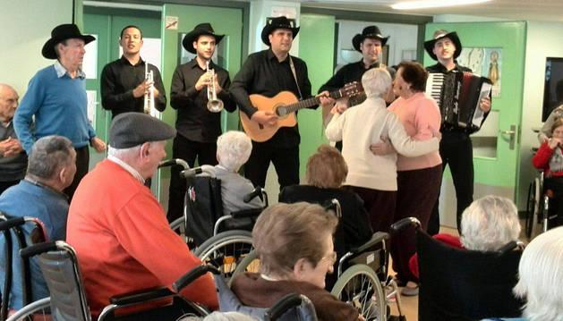 Varios residentes disfrutan de la música mexicana en Lumbier.