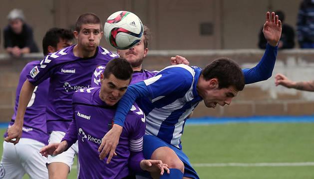 Maestresalas pelea por un balón aéreo ante la oposición de dos jugadores del Valladolid B.