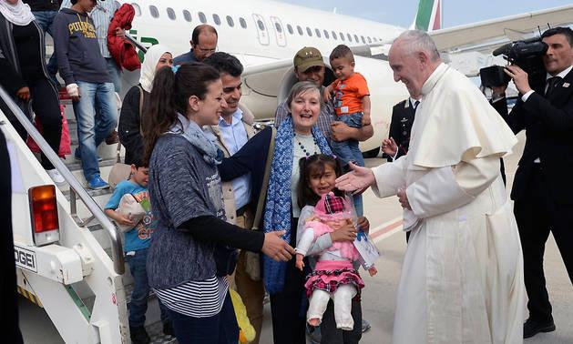 El papa Francisco saluda en el aeropuerto al grupo de 12 refugiados que acogerá el Vaticano.