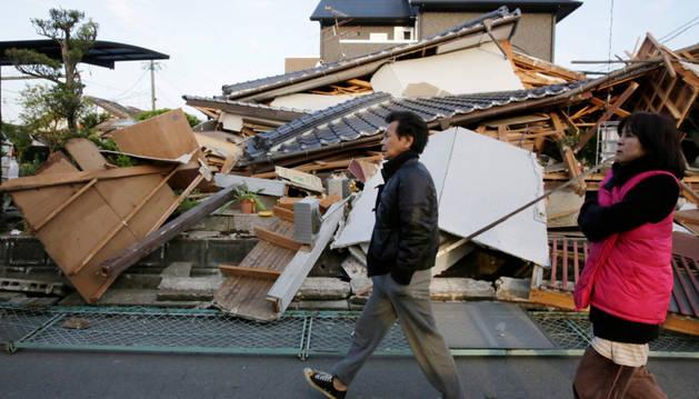 Un hombre y una mujer caminan junto a una casa dañada por el seísmo.