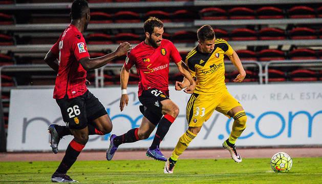 Álex Berenguer, que ayer disputó los 90 minutos del encuentro, se marcha con el balón controlado de Campabadal mientras Kassim Adams observa la jugada durante el partido celebrado ayer en el Iberoestar Estadio.