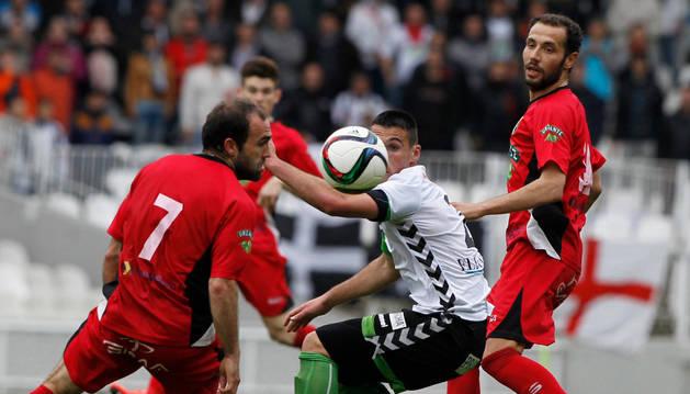 Paris y Óscar valero observan ayer el balón junto con un rival del Racing de Santander.