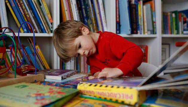 Una niño lee un libro en una biblioteca.