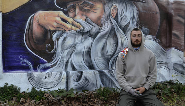El artista Pablo Nieva delante de una de sus creaciones en el muro del albergue de Los Arcos.