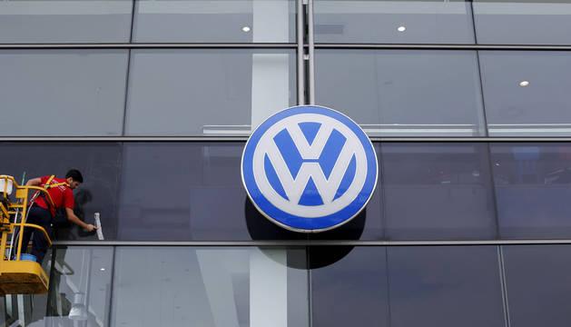 Un operario limpia la cristalera de un concesionario de Volkswagen.