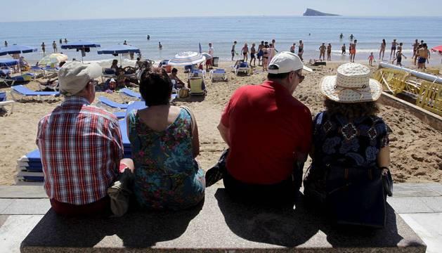 Unas parejas de jubilados disfrutan de sus vacaciones sentados en un acceso a una playa de las islas Canarias.