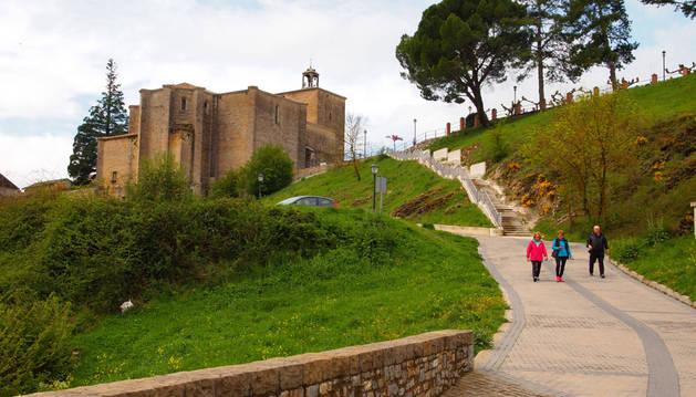 Paseantes camino del puente sobre el río Irati. Arriba, la iglesia que 'flanquean' dos árboles singulares.