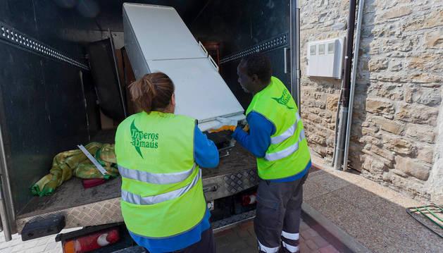 Empleados de Traperos de Emaús recogen un electrodoméstico.