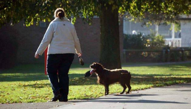 Una mujer que pasea con su perro acaba de recoger sus excrementos.