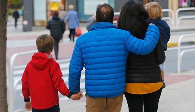 Una pareja con dos niños pequeños pasea por la calle en Pamplona.