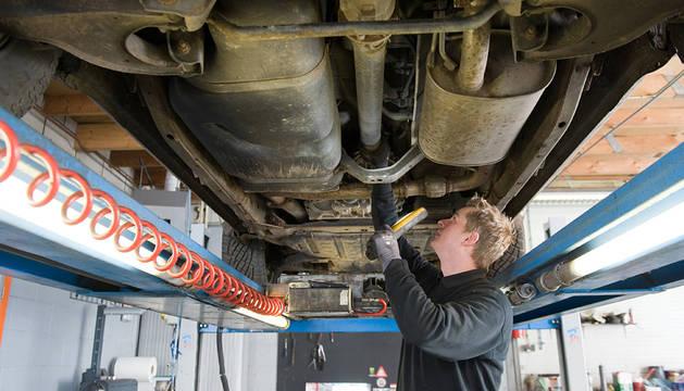 Una persona realiza la revisión de un coche.