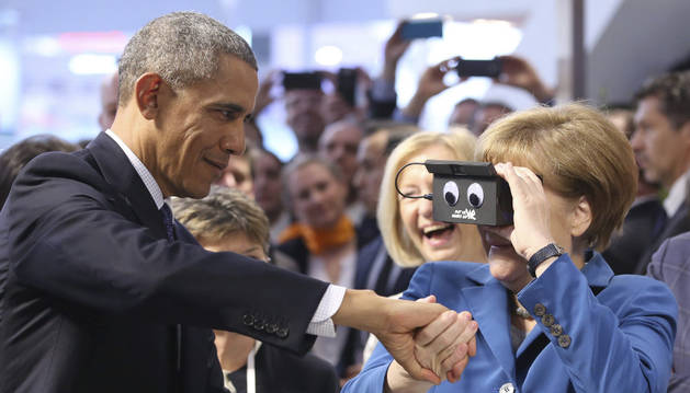 La canciller alemana, Angela Merkel (d), utiliza unas gafas de realidad virtual junto al presidente de Estados Unidos, Barack Obama.