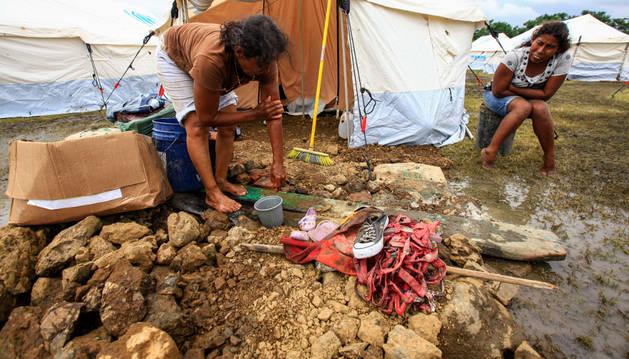 Mujeres lavan ropa afuera de una tienda en un centro de refugio para los damnificados del terremoto.