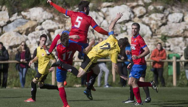 Dos jugadores del Idoya pugnan por un balón frente a uno del Zirauki, que cae derribado.