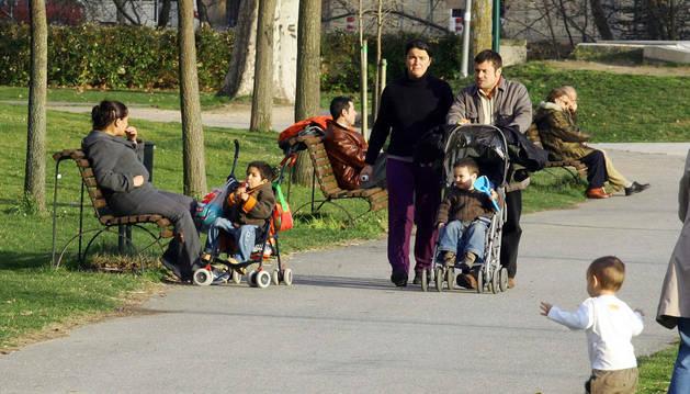 Varias familias paseando en un parque.