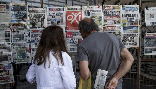 Dos ciudadanos miran un kiosko de periódicos.