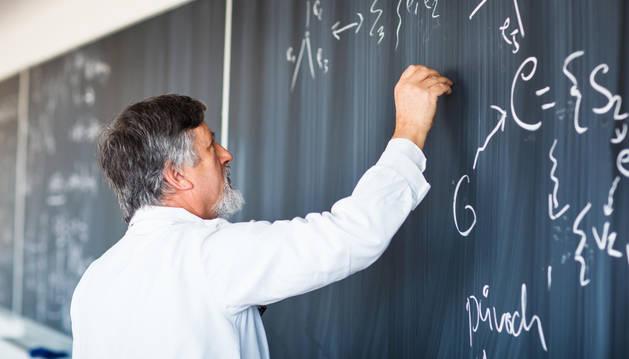 Un profesor escribe en una pizarra.