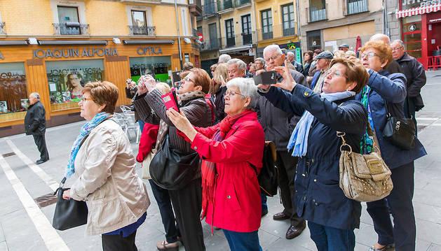 Un grupo de turistas, en la plaza del Ayuntamiento haciendo fotos a la casa consistorial.