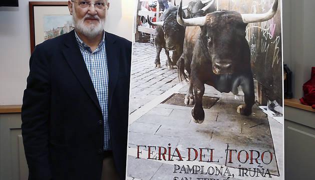 El fotógrafo Pío Guerendiáin posa junto al cartel que anunciará la Feria del Toro de San Fermín de 2016.