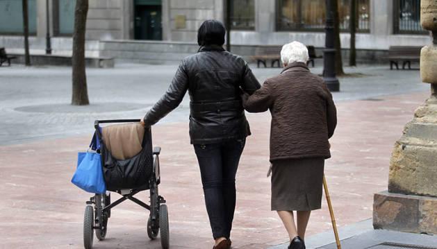 Una persona pasea con una anciana dependiente.