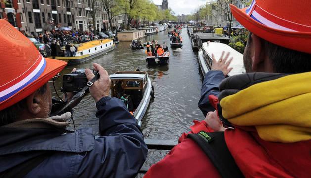 Varias personas hacen fotografía durante el Día del Rey en Amsterdam.