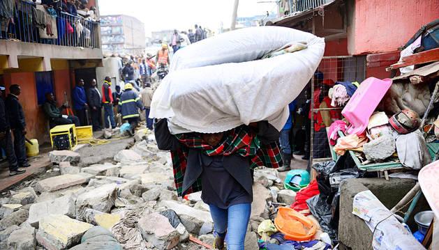 Una persona transporta un colchón entre los escombros del edificio.