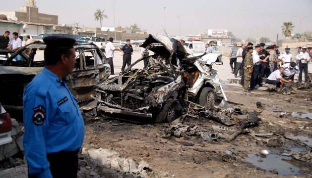 Agentes de policía iraquíes comprueban los daños tras un atentado con coche bomba.