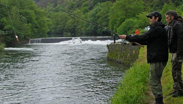 Dos pescadores, a orillas del río Bidasoa, con la presa del 'Pozo de los 50' de fondo.