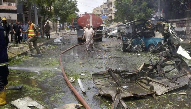 Miembros del cuerpo de bomberos trabajan tras un ataque en un distrito residencial de Alepo.