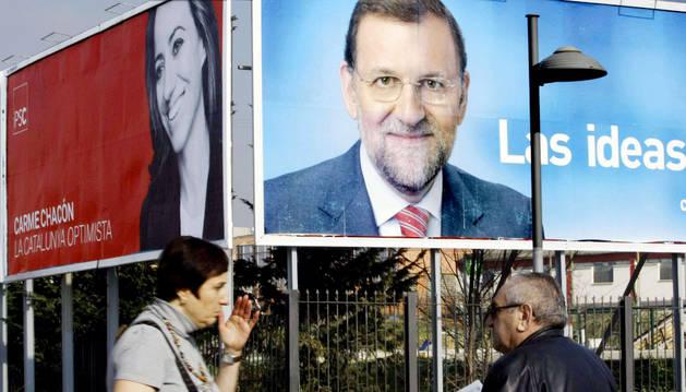 Dos viandantes ante una valla publicitaria de Mariano Rajoy.