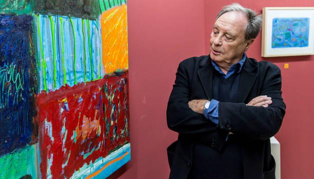"""El pintor, periodista y escritor Vicente Verdú posa ante uno de las veinte obras que forman la exposición """"El silencio del color"""" en la Galería Conde Rodezno."""