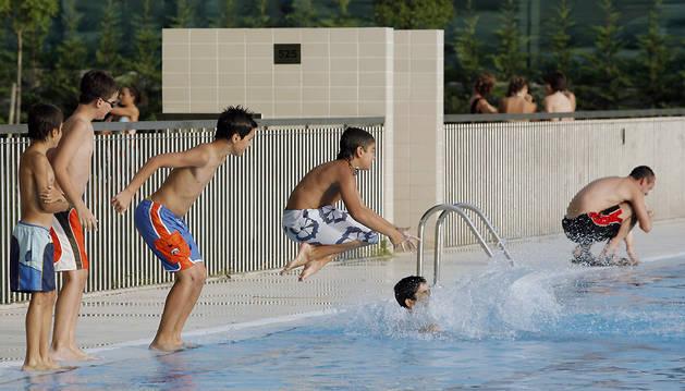 Unos niños se tiran a la piscina en las piscinas de la Chantrea.