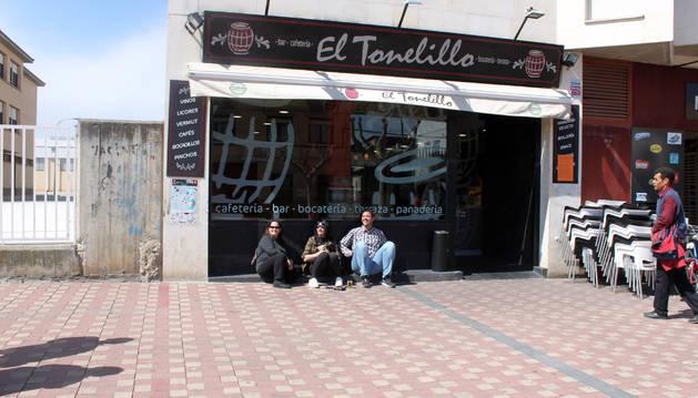 Varias personas, sentadas en el suelo a las puertas de un bar, con la terraza recogida a la derecha.