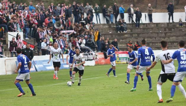 Un jugador del Tudelano conduce la pelota ante la mirada de sus contrincantes y compañeros.