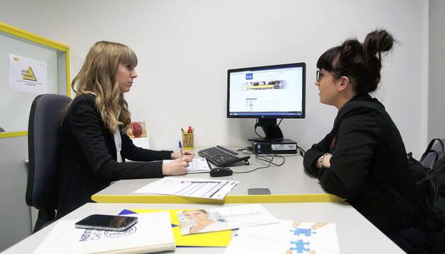 Una técnica de empleo atiende a una joven desempleada en las oficinas de Flexiplán en la calle Íñigo Arista de Pamplona.