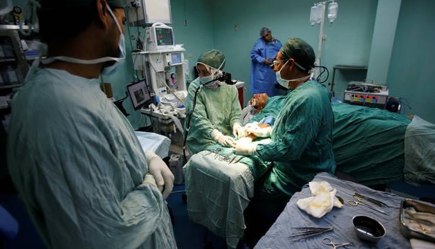 Varios médicos y enfermeros, durante una operación.