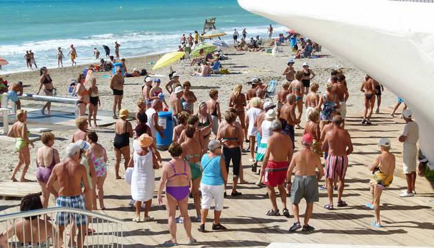Jubilados pasean y disfrutan en una playa de Benidorm (Alicante).