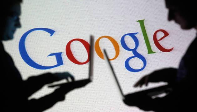 Varias personas con sus ordenadores frente a una proyección del logo de Google.