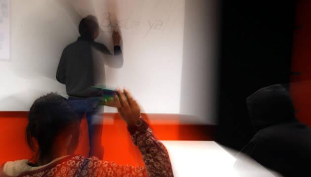 Imagen de un profesor siendo agredido por un alumno, que intenta lanzar un objeto.
