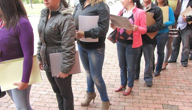 Una cola de jóvenes con su currículum vitae para entregar en una empresa .