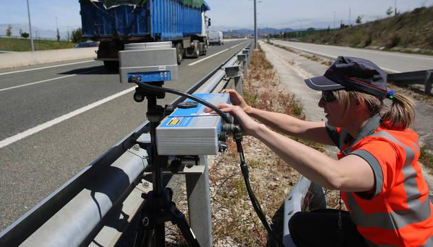 Una agente de la Policía Foral indica a un vehículo que reduzca la velocidad en el acceso a Pamplona desde Zizur.