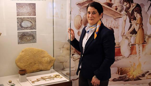 Belén Chocarro, guía del Museo Arqueológico Las Eretas, junto a los restos de un bebé al que se enterró con un vaso de cerámica. Detrás, ilustración que muestra cómo se llevaba a cabo el ritual de enterramiento, al calor del hogar.