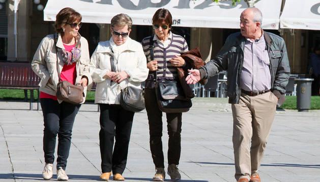 Un grupo de cuatro personas pasea por la Plaza del Castillo de Pamplona.
